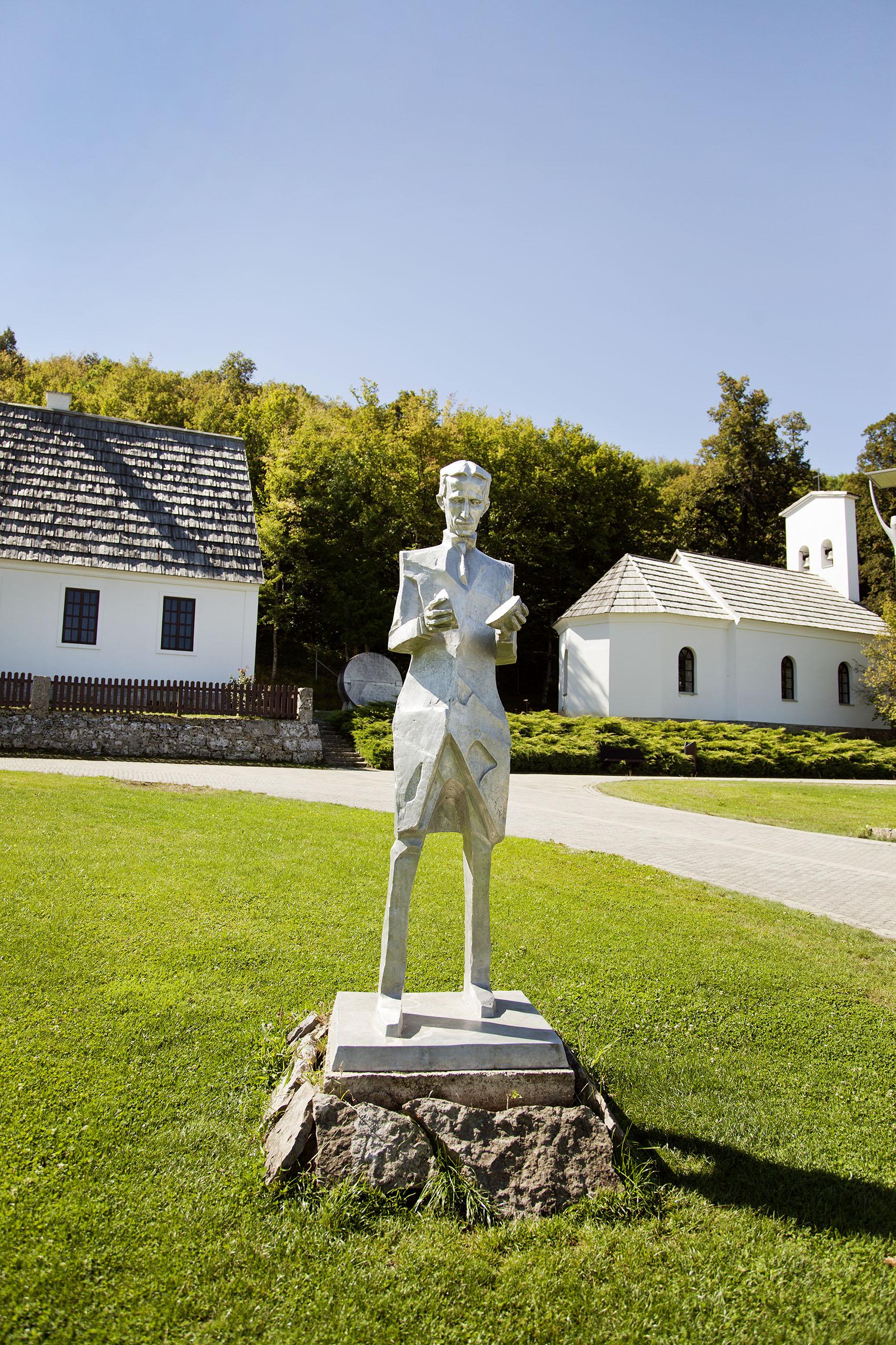 Kroatien; Tesla; Smiljan, Geburtsort von Nikola Tesla; Nikola Tesla Statue mit dem Geburtshaus im Hintergrund