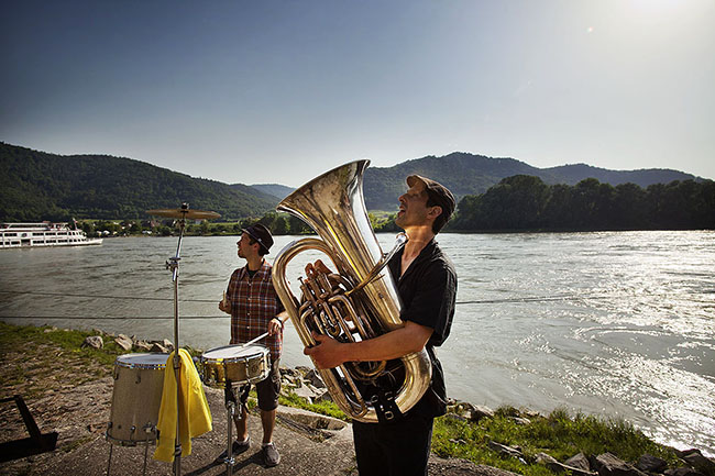 "Austria; Lower Austria, Wachau, E-Bike Cycling Tour trough the Wachau; Dürnstein; Musicians of the music festival ""Glatt und Verkehrt"" playing on the riverside of the Danube"