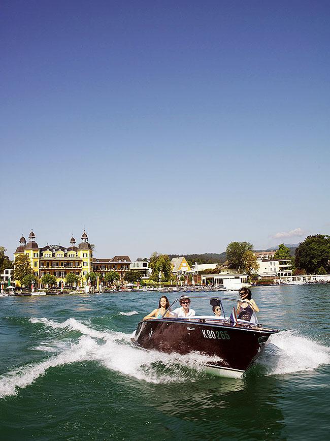 Austria; Carinthia; Wörthersee, Velden, Junge Leute bei einer Motorbootsausfahrt vor dem Hotel Schloss Velden  ©  Reiner Riedler